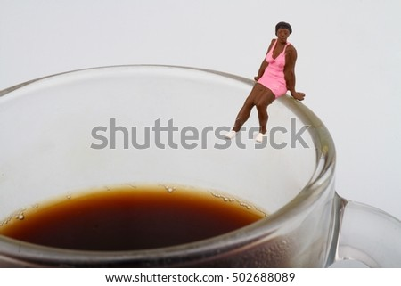 Miniature of a black woman sitting on a cup of coffee