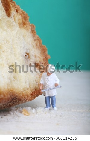 Miniature of a chef with bread on a wooden cutting board - stock photo