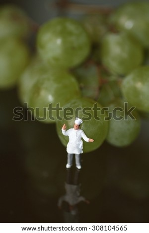 miniature of a chef with grapes - stock photo