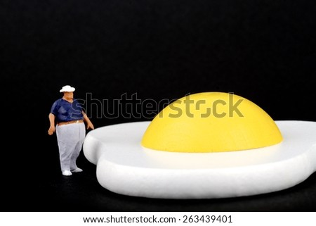 miniature of a fat man over the top of a fried egg - stock photo