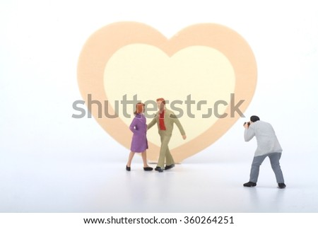 Miniature of a photographer taking pictures of a young couple with a pink and yellow heart as background - stock photo