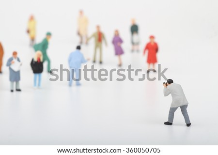 Miniature of a street photographer taking pictures of strangers walking on ta white background - stock photo