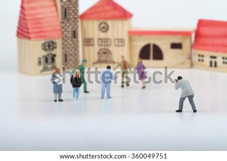 Miniature of a street photographer taking pictures of strangers walking on the streets of a city - stock photo