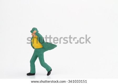 miniature of an elegant man walking against the wind on a white background - stock photo