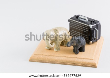 Miniature of an elephant and the suitcase - stock photo