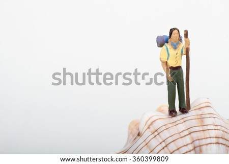 Miniature of an hiker on a big shell - stock photo