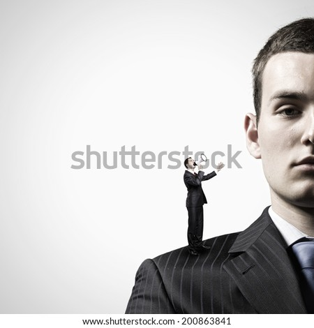 Miniature of businessman screaming in megaphone standing on boss shoulder - stock photo
