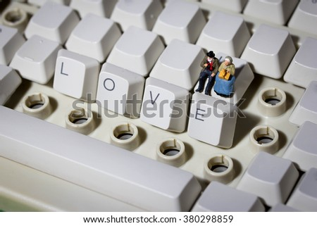miniature old people on letter keys close up, concept of love