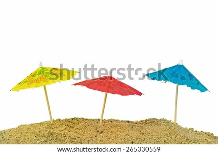 Miniature paper sun umbrellas in sand with white background and copy space for your text - stock photo