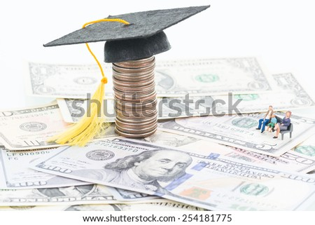 Miniature parents saving for their child's future education fund  - stock photo
