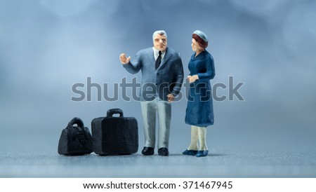 Miniature people - a couple waiting in the airport lobby - stock photo