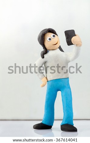 miniature people, a teenage girl makes a selfie. - stock photo