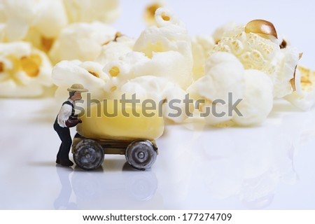 Miniature people at work with corn and popcorn - stock photo