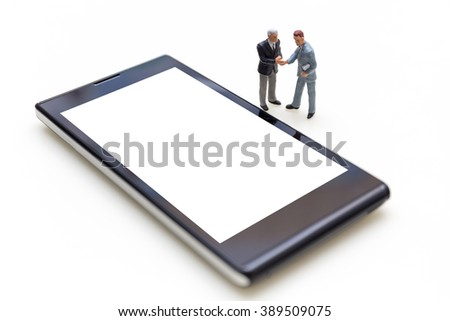 Miniature People Business Concept : Two Miniature Businessmen Handshaking For Agreement With Blank Mobile Phone - stock photo