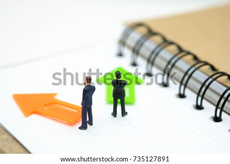Miniature people: Businessman standing in front of arrow pathway choice using as Business decision concept.