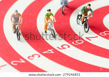 Miniature people cycling on darts - stock photo