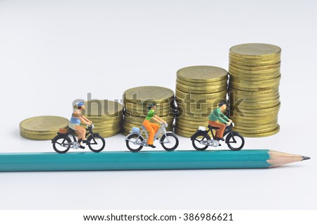 Miniature people cycling on pencil and stack of coins background - stock photo