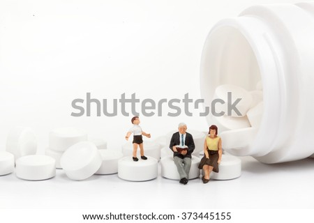 miniature people - Elderly people posing in front of pills  - stock photo