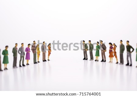 Miniature people in two lines across to each other over white background.