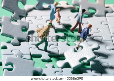 Miniature people on a jigsaw puzzle in windstorm