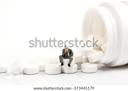 miniature people - people posing in front of pills  - stock photo