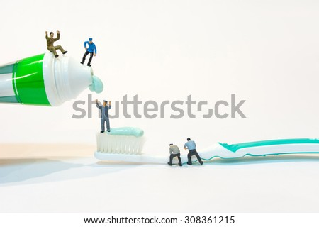 Miniature people squeeze toothpaste - stock photo