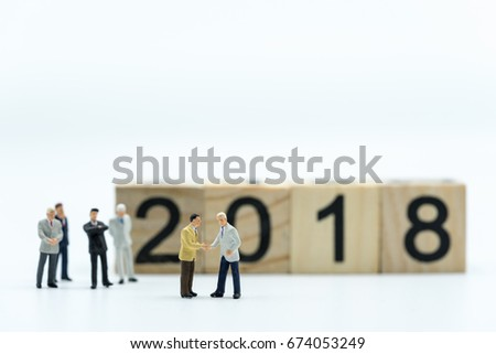 Miniature people: Two confident business man shaking hands during a meeting with wooden block 2018 text as background, success, dealing, greeting and partner concept.