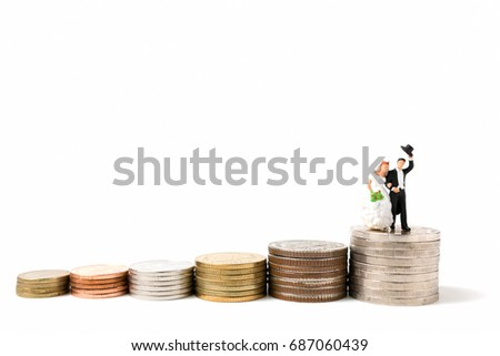 Miniature people wedding , bride and groom couple on stack coins  on white background.