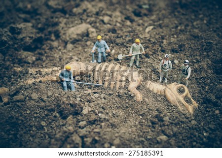 Miniature People with dinosaur fossil in vintage color tone - stock photo