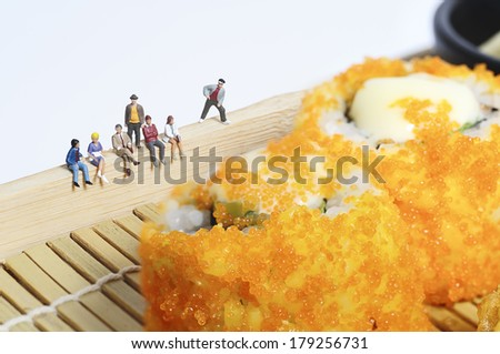 Miniature people with sushi - stock photo