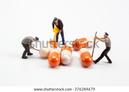 miniature people  - worker moving capsules pills