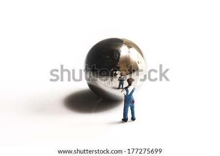 Miniature peoples work with metal ball - stock photo