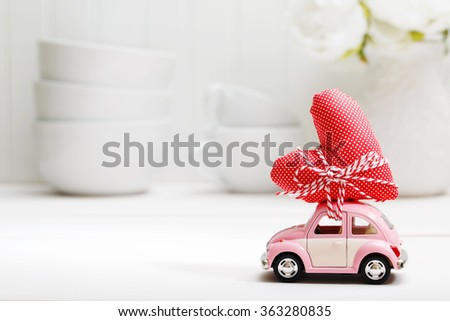 Miniature pink car carrying a red heart cushion  - stock photo