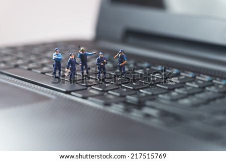 Miniature police squad protecting laptop computer. Technology concept - stock photo