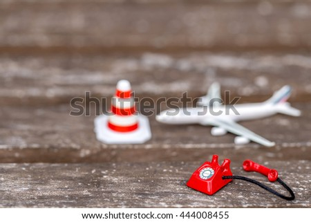 miniature red vintage telephone and airplane model with traffic cone on grunge wooden floor. - stock photo