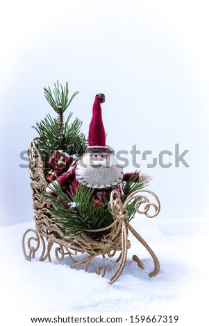 Miniature Santa Claus on a sleigh with gifts. - stock photo