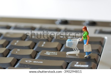 Miniature shopper with shopping cart on a computer keyboard - stock photo