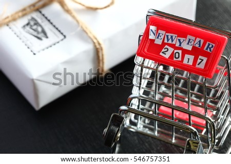 Miniature shopping cart model and new year 2017 wording cut from small piece of paper on the front part of shopping cart.