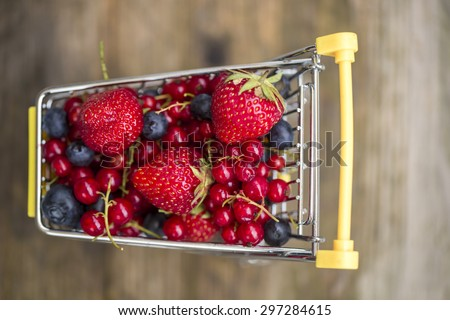 Miniature shopping cart with strawberries, blueberries and redcurrants - stock photo