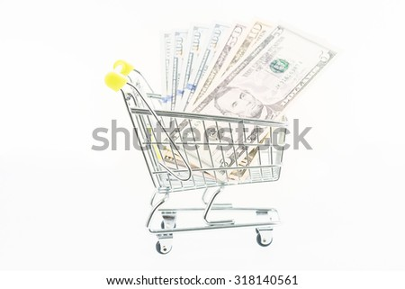 Miniature shopping cart with US dollar banknotes close up - stock photo