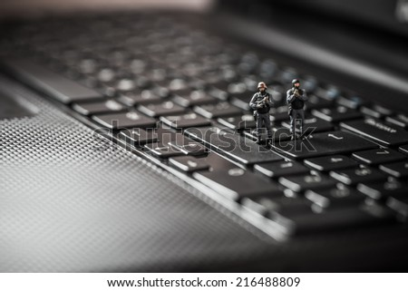 Miniature swat squad protecting laptop computer. Technology concept - stock photo
