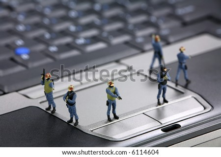 Miniature swat team are guarding a laptop from viruses, spyware and identity thieves. Computer security concept. - stock photo