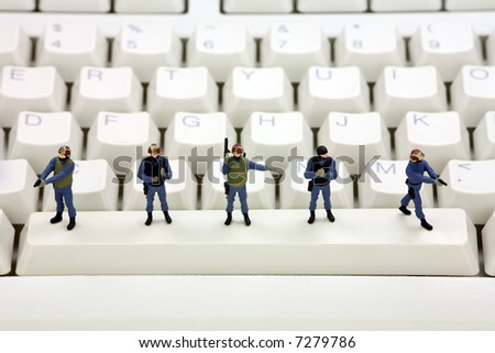 Miniature swat team is standing on a computer keyboard guarding it from viruses, spyware and identity thieves. Computer security concept. - stock photo