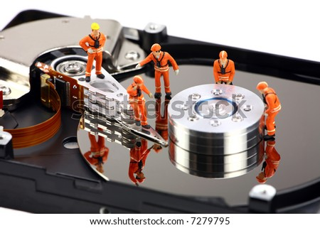 Miniature technicians closely inspecting a hard drive for viruses, spyware and trojans. Computer technician concept. - stock photo
