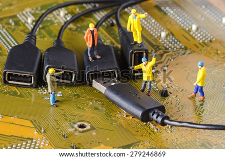 Miniature Technicians try to connecting data cable - stock photo