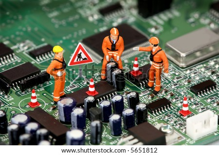 Miniature technicians working on a computer circuit board or motherboard. Tech support concept. - stock photo