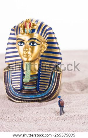 Miniature tourist with the Egyptian King Tutankhamen statue on sand close up - stock photo