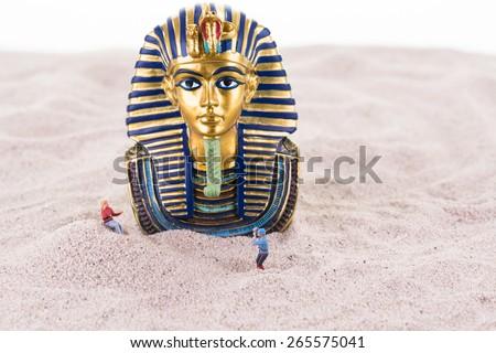 Miniature tourists with the Egyptian King Tutankhamen on sand close up - stock photo