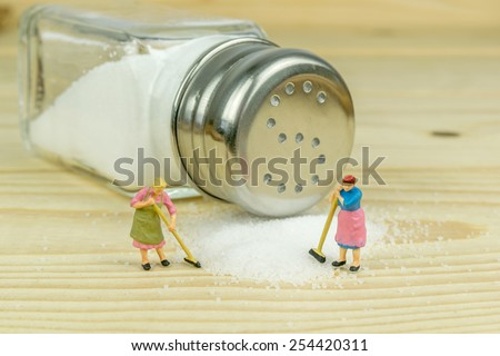 Miniature toy housewives figures cleaning up spilled salt on wooden table - stock photo