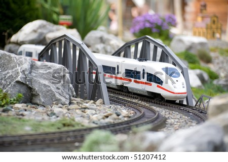 Miniature toy model of modern train crossing bridge - stock photo